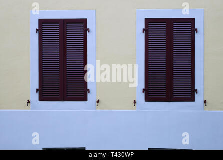 Details of old medieval style building. The building has grey concrete walls and the window frames white & purple and made of wood. - Stock Image