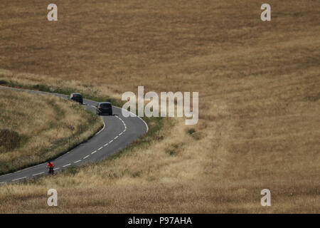 Beachy Head, UK - July 14 2018: A road cuts through the Eastbourne Downland Estate grasslands by the hilltop of the chalk sea cliff at Beachy head on a hot summers day on 14 July 2018. Temperatures raised to 27 degrees and is expected to stay high for another month. The cliff, the highest chalk sea cliff in Britain rises to 162 metres above sea level and unfortunately one of the most notorious suicide spots in the world. Credit: David Mbiyu - Stock Image