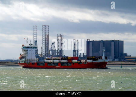 Container ship A2B SPIRIT  IMO:9144689, departing from Teesport England UK passing Jack up drilling rigs and Hartlepool Nuclear power station - Stock Image