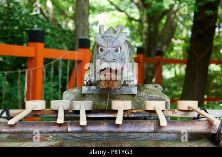 Dragon statue in ceremonial washing of hands basin in Fushimi Inari Shrine in Kyoto, Japan. - Stock Image