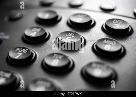 Modern black business landline telephone keypad buttons close-up. - Stock Image