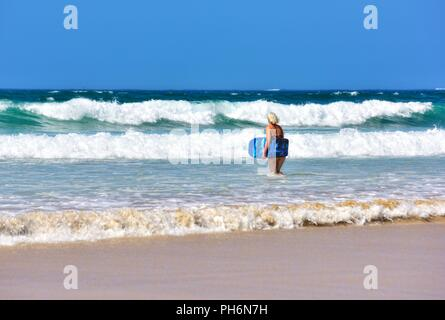 Blond woman walking into the sea with a body board,Riviere Towans beach,Riviere Towans beach, Phillack, Hayle,cornwall,England,UK - Stock Image