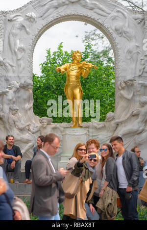 Tourists Vienna, view of a group of tourists taking a selfie photo in front of the golden Strauss statue in the Statdtpark in Vienna, Wien, Austria. - Stock Image