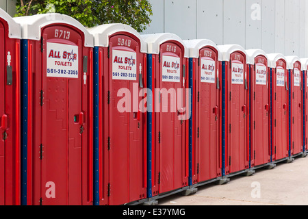 Row of red portable toilet facilities at a special public event in Miami, Florida, USA. - Stock Image