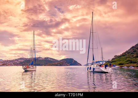Yachts anchored over the calm sea at sunset in gumsuluk bay in Bodrum, Mugla, Turkey. - Stock Image