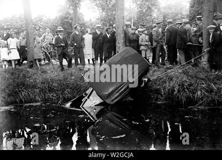 Traffic accident with passenger car in a canal, with many spectators ca. 1930s Netherlands - Stock Image