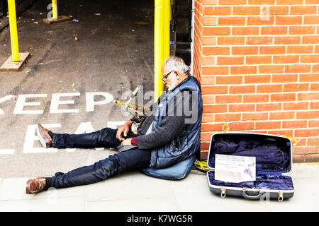 Down on his luck musician, saxophone player resting, busker resting, busker sleeping, saxophonist, having a rest, resting on street, sleeping outside - Stock Image