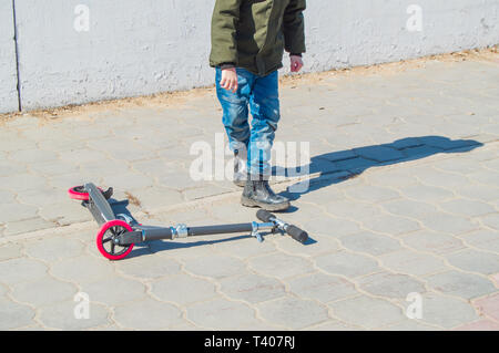 Teen boy in a green jacket and jeans lifts your scooter after a fall in the open in the Park, children's entertainment in the fresh air. - Stock Image