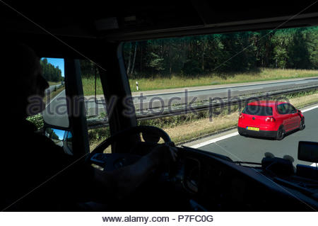 Truck driver being overtaken by a red VW car, heading north on the A3 autobahn in Germany. - Stock Image