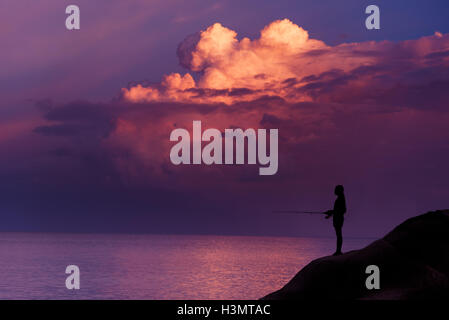 Young girl fishing at sunset on the island of rock - Stock Image