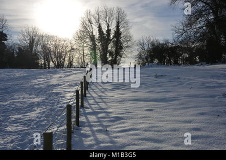 View of a fence in a snow covered field in the north Oxfordshire village of Hook Norton - Stock Image