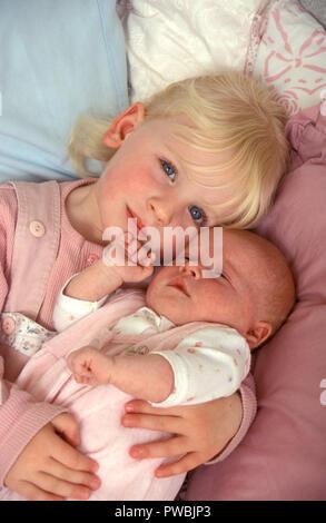 little girl holding her newborn baby sister - Stock Image