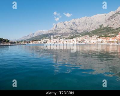 Calm blue sea on sunny day and Makarska city below mountain Biokovo in Croatia - Stock Image