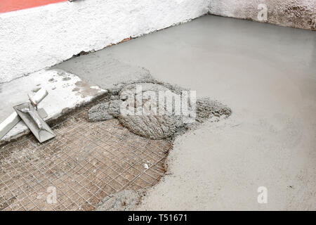 Process of making concrete floor with new portion of mixed concrete ready for flattening with hand tools - Stock Image