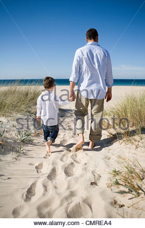 Father and son walking on beach - Stock Image