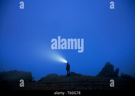 Small silhouette of man with headlamp stands in foggy dusk - Stock Image