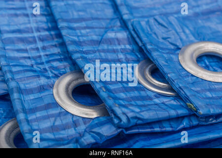 Blue LDPE protective tarpaulin with aluminium eyelet. Metaphor 'protection', building industry. - Stock Image