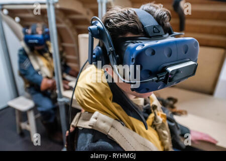 London, UK. 14th March, 2019. Re-enactors have a go at the VR experience - Immersive Histories: Dambusters Virtual Reality Experience. An opportunity to step back in time to the early hours of 17 May 1943 and on board Avro Lancaster G-George to join the Dambusters on their legendary mission. Using the latest virtual reality and haptic technology, in conjunction with a physical 1:1 recreation of the interior of the iconic Avro Lancaster bomber. Credit: Guy Bell/Alamy Live News Credit: Guy Bell/Alamy Live News - Stock Image