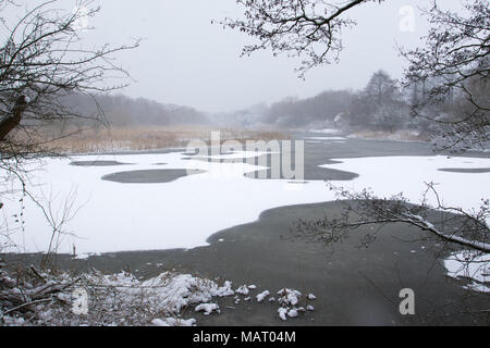 view over a snow-covered frozen lake during a snow shower at Attenborough Nature Reserve, Nottinghamshire - Stock Image