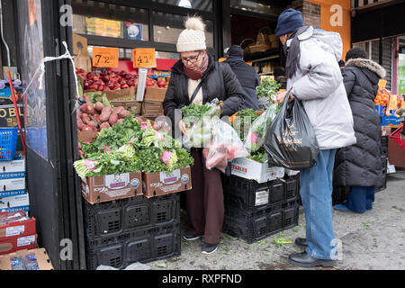 A street scene in Jackson Heights Queens, New York featuring a couple buying groceries from a store's outdoor stand. - Stock Image