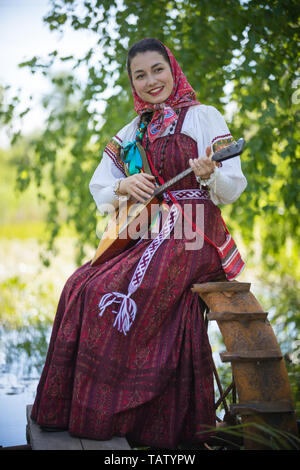 Young romantic woman in traditional russian clothes sits on the small pier near the lake, and play music on balalaika - vertical shot - Stock Image