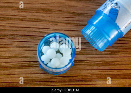 Homeopathic globules scattered around with their colored containers in the shape of tube on a wooden table - Stock Image