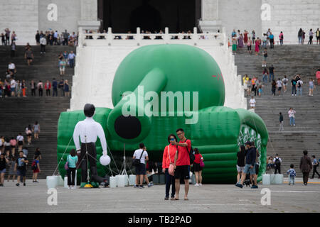 A couple taks a selfie in front of a Tank Man installation at Chiang Kai-shek Memorial Hall in Taipei. - Stock Image