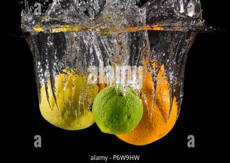 An orange, lemon and a lime splashing into water on a black background. - Stock Image