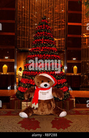 Teddy b ears and Christmas tree decoration traditional in the foyer of the Conrad Hotel, Singapore - Stock Image