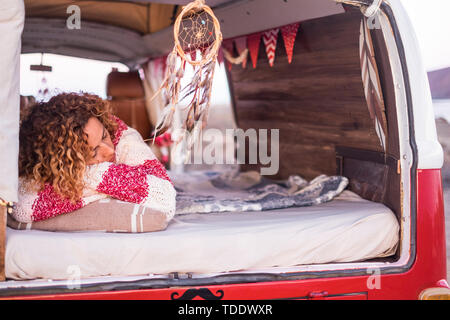 Vanlife lifestyle and travel concept with beautiful curly caucasian woman sleeping inside a red old vintage van  young people traveling with camper -  - Stock Image