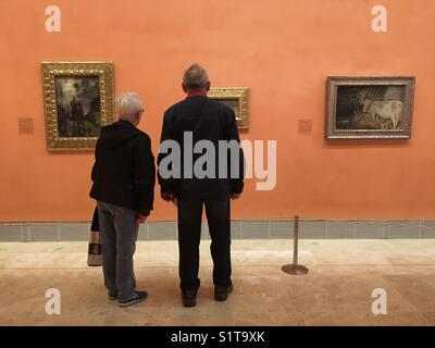 Senior couple at art gallery in Spain looking at painting - Stock Image