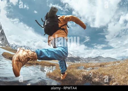 Hiker jumps across water in mountains area. Hiking concept with man - Stock Image