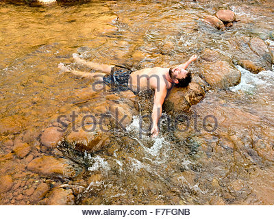 Mid 30's man male cools off in Bright Angel Creek at Phantom Ranch after hiking down the North Kaibab Trail, - Stock Image