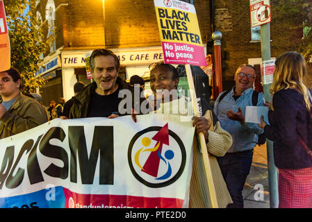 London, UK. October 9th 2018. People hold the Stand Up to Racism banner at the rally outside the New Atlas Cafe Restaurant where a young black man was attacked by police who used obviously unnecessary force when arresting him on suspicion of having been involved in a knife attack. He was assaulted by six officers, and was viciously kicked while officers struggled to handcuff him, andwhen he was well under control and held on the ground he was sprayed in the face with CS gas. Credit: Peter Marshall/Alamy Live News - Stock Image
