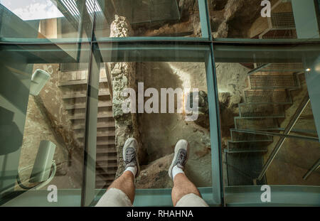 Cartagena, Spain - September 14th, 2018: Glass floor of Punic Wall Interpretation Center. Visitor view under his feet - Stock Image
