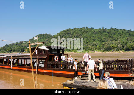 Tourists boarding a traditional wooden boat for a cruise up the Mekong River from Luang Prabang, Laos, southeast Asia - Stock Image