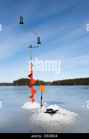 Hand ice auger and tip-up ice fishing rod , Finland - Stock Image
