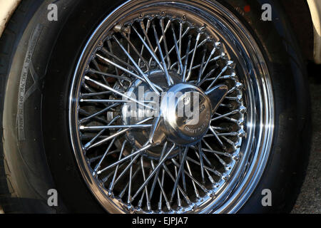 A spoked wire wheel on a vintage car. - Stock Image