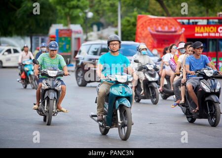 Moped riders in Hanoi, Vietnam. A ban on motorbikes and scooters has been set to 2030 by the city council and the department of transport. - Stock Image
