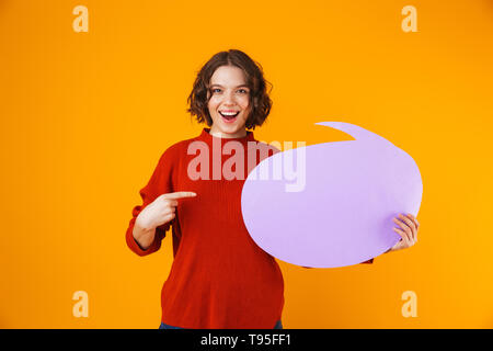 Image of joyous girl 20s wearing sweater holding thought bubble with copyspace while standing isolated over yellow background - Stock Image