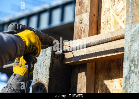 Putting some screws in a piece of wood. Screw twists on the floor - Stock Image