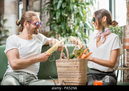 Young vegetarian couple sitting on the sofa with bag full of fresh vegetables in the beautiful home interior - Stock Image