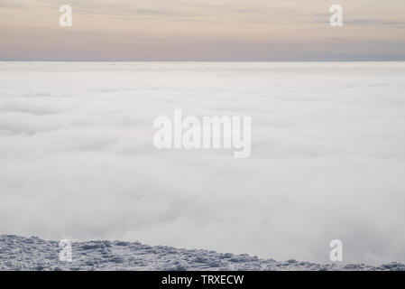 Above white heavy clouds. Panorama of cloudscape from the top of the mountain. - Stock Image