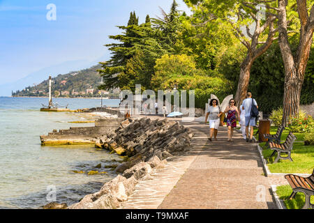 TORRI DEL BENACO, LAKE GARDA, ITALY - SEPTEMBER 2018: People in Torri del Benaco on Lake Garda walking on the footpath around the lake. - Stock Image