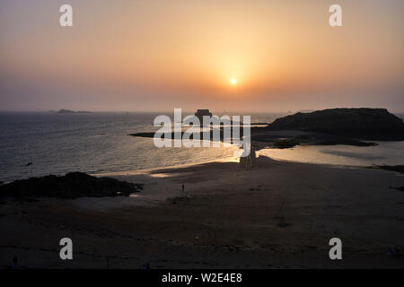 Sunset over small island and tidal causeway at St Malo, Brittany, France - Stock Image