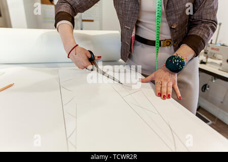Women's hands cut the pattern out of paper with tailors' scissors on a white table - Stock Image