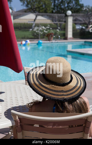 Young woman in a bikini and hat sitting relaxing by a community swimming pool  on a hot summers day in Southern California. - Stock Image