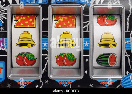 Close up detail of a fruit machine with three bell symbols - Stock Image