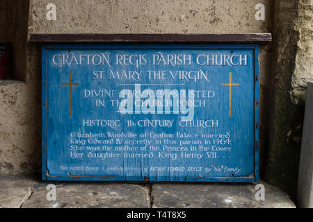 Weather beaten wooden sign for the church of St Mary The Virgin, an 11th century historic church in the village of Grafton Regis, UK - Stock Image