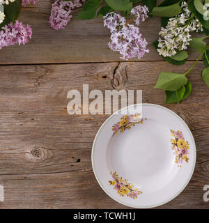 Plate and decor of flowers on the background of vintage wooden planks.Vintage background with lilac flowers and place under the text. View from above. - Stock Image